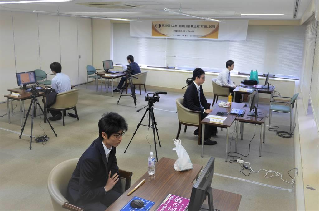 「第25回LG杯朝鮮日報棋王戦」のインターネット対局に臨んだ村川大介十段(右奥)らは、間隔をあけてパソコンに向き合った