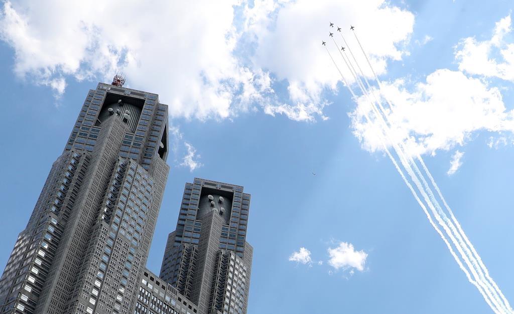 新型コロナウイルス感染症への対応にあたる医療従事者に敬意を示すため、都心を飛行したブルーインパルス。左は都庁=5月29日午後、東京都新宿区(福島範和撮影)