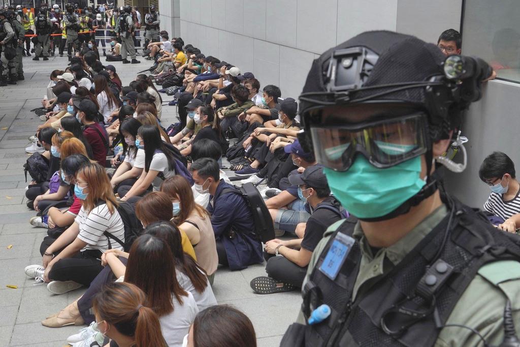 拘束されたデモ参加者らと香港警察の隊員(手前)=5月27日、香港(AP)