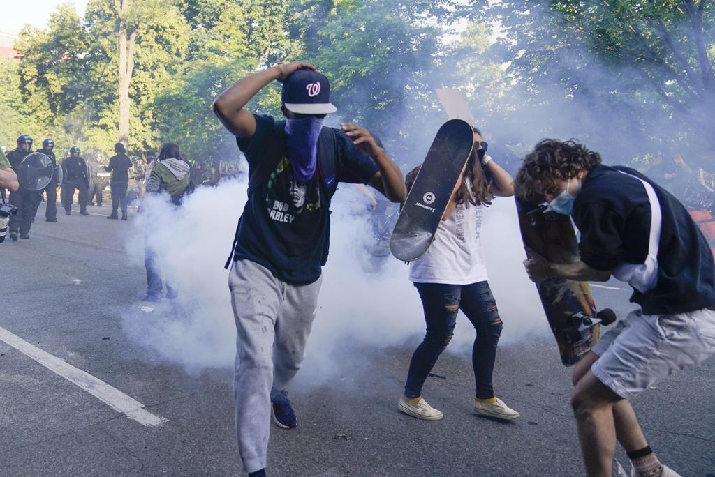 1日、米ワシントンのホワイトハウス近くで、催涙ガスを避けようとする抗議デモの参加者ら(AP=共同)
