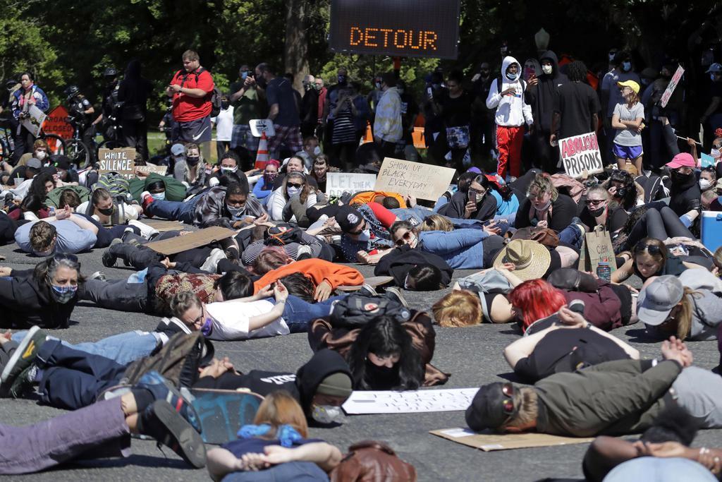 1日、米ワシントン州で、白人警官による黒人男性暴行死事件を巡り、道路に寝そべって抗議する人々(AP=共同)