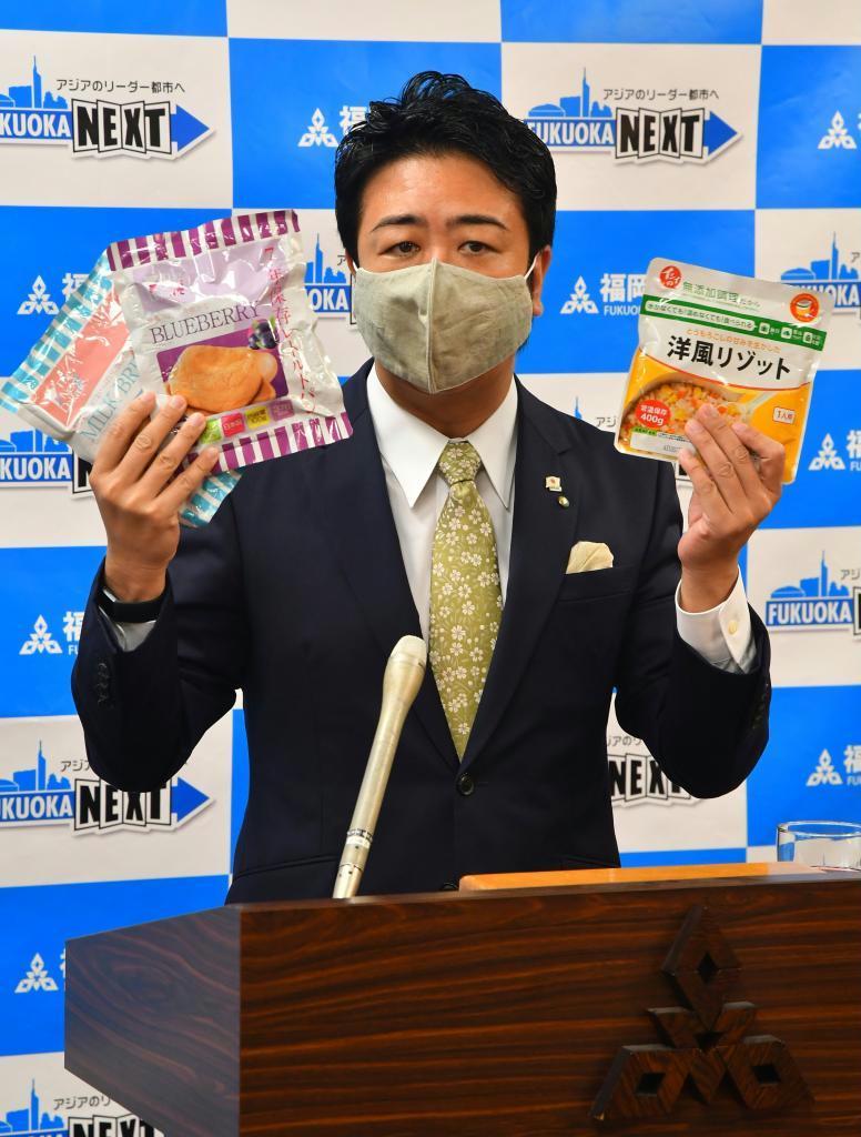 防災備蓄食料を手にする福岡市の高島宗一郎市長