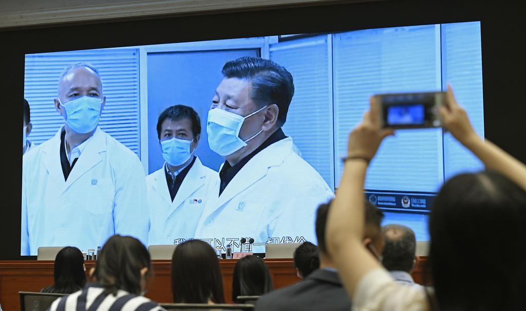 7日、中国政府が公表した新型コロナウイルス感染症に関する白書について、記者会見場で習近平国家主席の映像にカメラを向ける報道関係者ら=北京(共同)