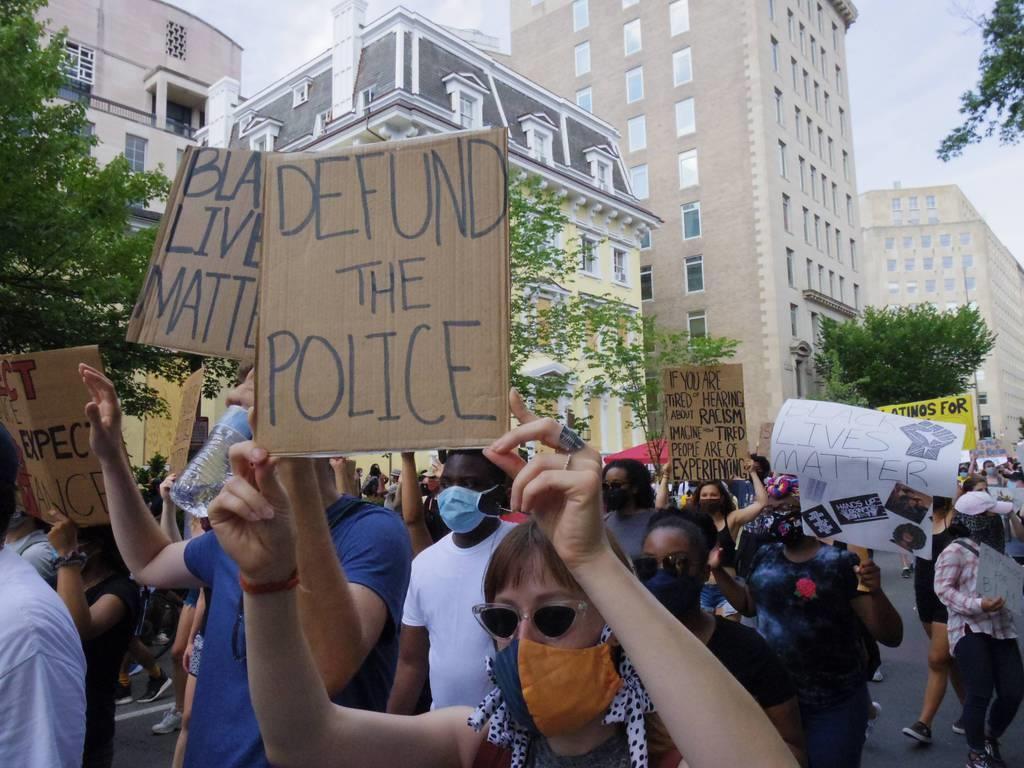 首都ワシントンで「警察予算を打ち切れ」のプラカードを掲げて行進するデモ参加者(黒瀬悦成撮影)