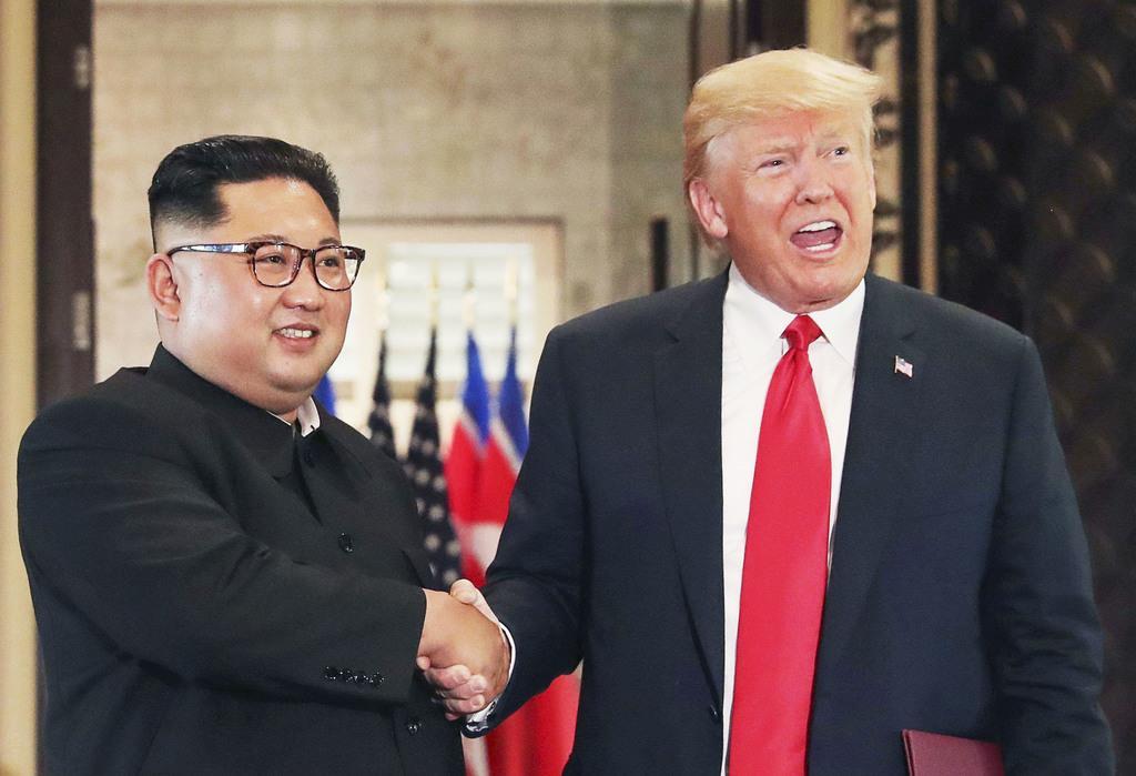 2018年6月、米朝首脳会談の共同声明の署名式で握手する北朝鮮の金正恩朝鮮労働党委員長(左)とトランプ米大統領=シンガポール(ロイター)