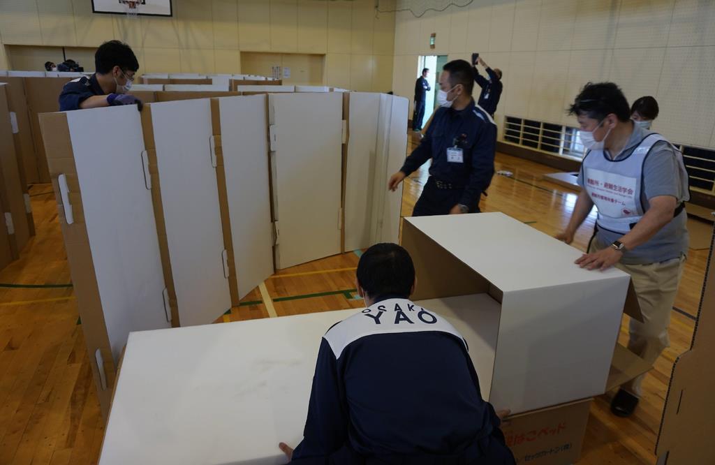 避難所での感染症対策を視野に、段ボール製のベッドや間仕切りを設置する訓練を行う大阪府八尾市の職員ら=5月20日、八尾市