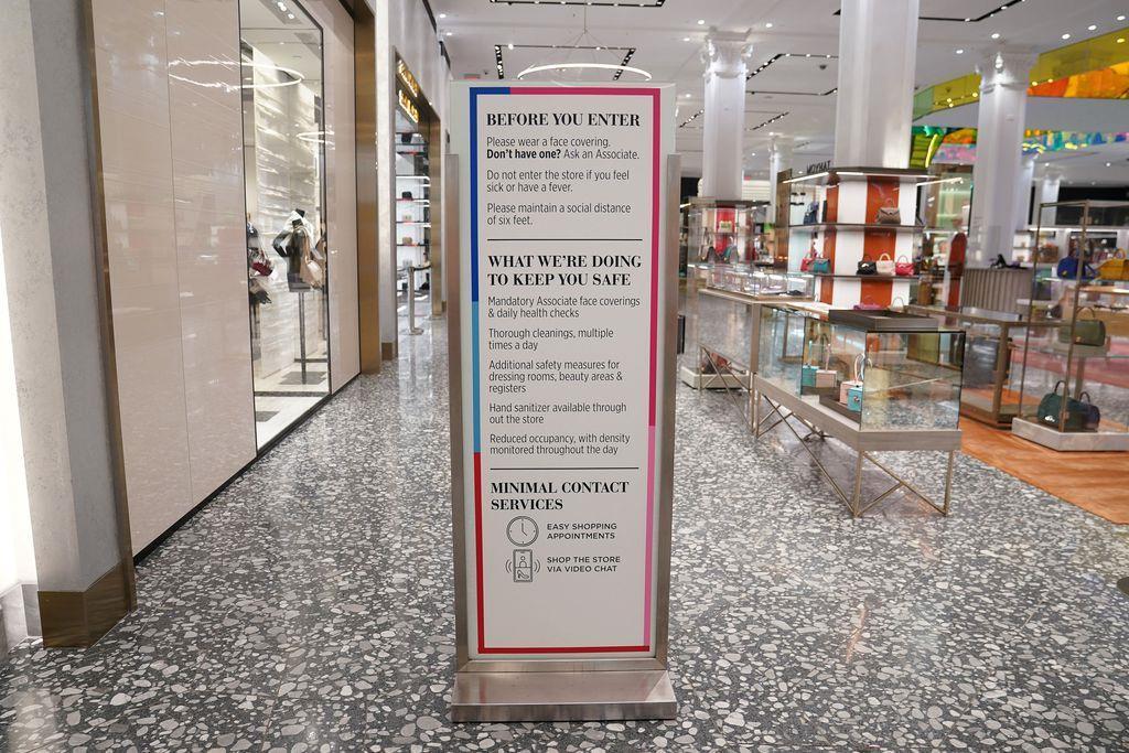 ニューヨーク・マンハッタンにある高級百貨店サックス・フィフス・アベニューの入り口に立つ新型コロナウイルス感染予防対策の呼びかけ=24日(ロイター)