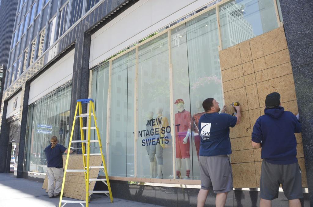 営業再開に伴い、略奪防止の木の板が取り外される服飾店=8日、米ニューヨーク市(共同)
