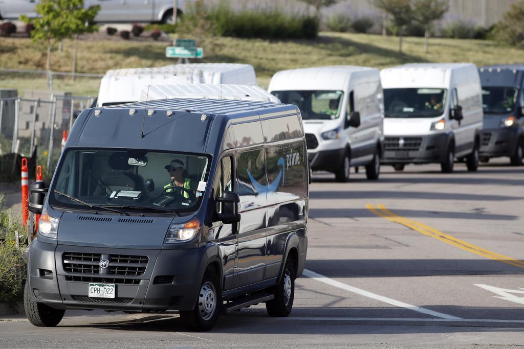 アマゾンの配送センターを出発する配送車=米コロラド州イングルウッド郊外(AP)