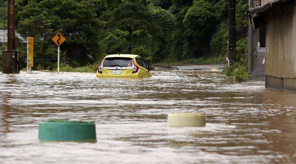 水に漬かった道路で立ち往生する車=4日午前9時38分、熊本県八代市