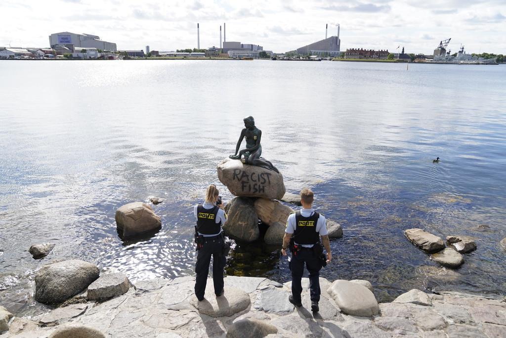 落書きされた人魚姫の像の現場を確認する警察官ら=3日、デンマークのコペンハーゲン(Ritzau Scanpix・AP)