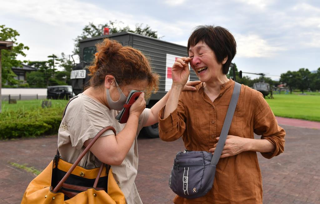 自衛隊のヘリで救出された熊本県八代市坂本町の女性(右)。知人との再会を喜んだ=5日午前8時28分、同市の会地公園(沢野貴信撮影)