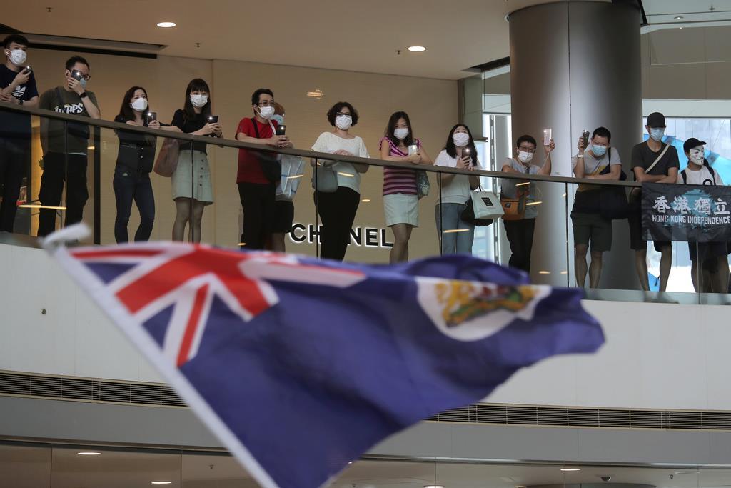 ショッピングモールで香港の植民地の旗を振り、デモのテーマソング「香港に栄光あれ」を歌う人たち=5月29日、香港(AP)