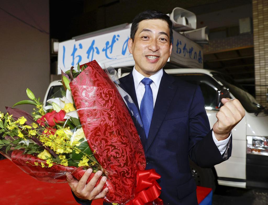 鹿児島県知事選で当選が決まり、花束を手に笑顔の塩田康一氏=12日夜、鹿児島市