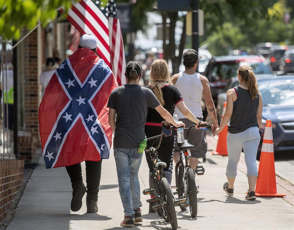 南軍旗を羽織って歩く男性(左)=米バージニア州マリオン(Bristol Herald Courier・AP)