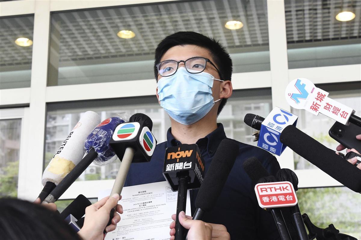 20日、香港・九竜地区で立法会選挙への立候補届け出を前に記者会見する民主派の黄之鋒氏(共同)
