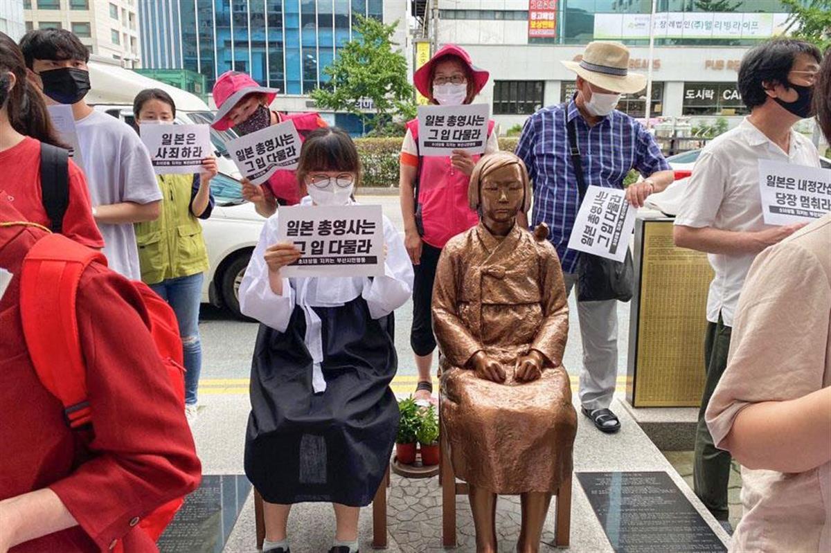 韓国・釜山に設置された従軍慰安婦問題を象徴する少女像のそばで集会を開く市民団体=11日(市民団体提供・聯合=共同)