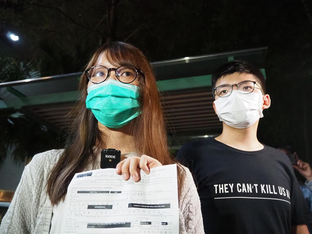 11日、保釈後に香港の警察署前で記者会見する周庭氏(左)(藤本欣也撮影)