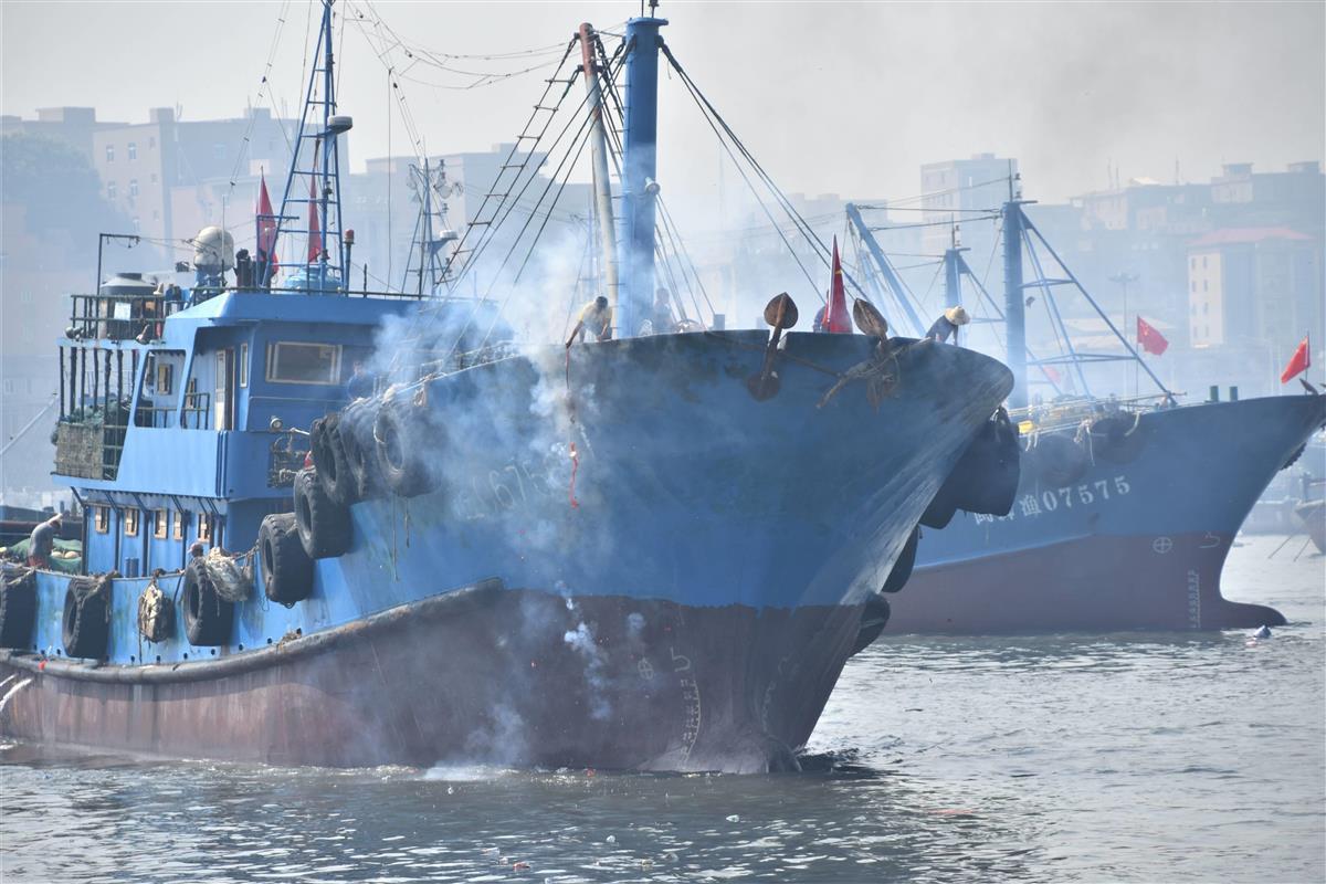 8月16日、中国福建省石獅の祥芝港で、出漁を祝う爆竹を鳴らしながら港を出る漁船。東シナ海の漁解禁を受けて、一部は尖閣諸島沖に向かう可能性もある(西見由章撮影)