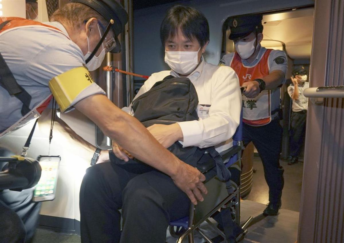 人身事故を想定した訓練で、緊急停止した新幹線から車いす用スロープで対向列車に避難する乗客役のJR九州の社員=14日未明