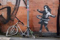 バンクシー新作、一部不明 柱につながれた自転車