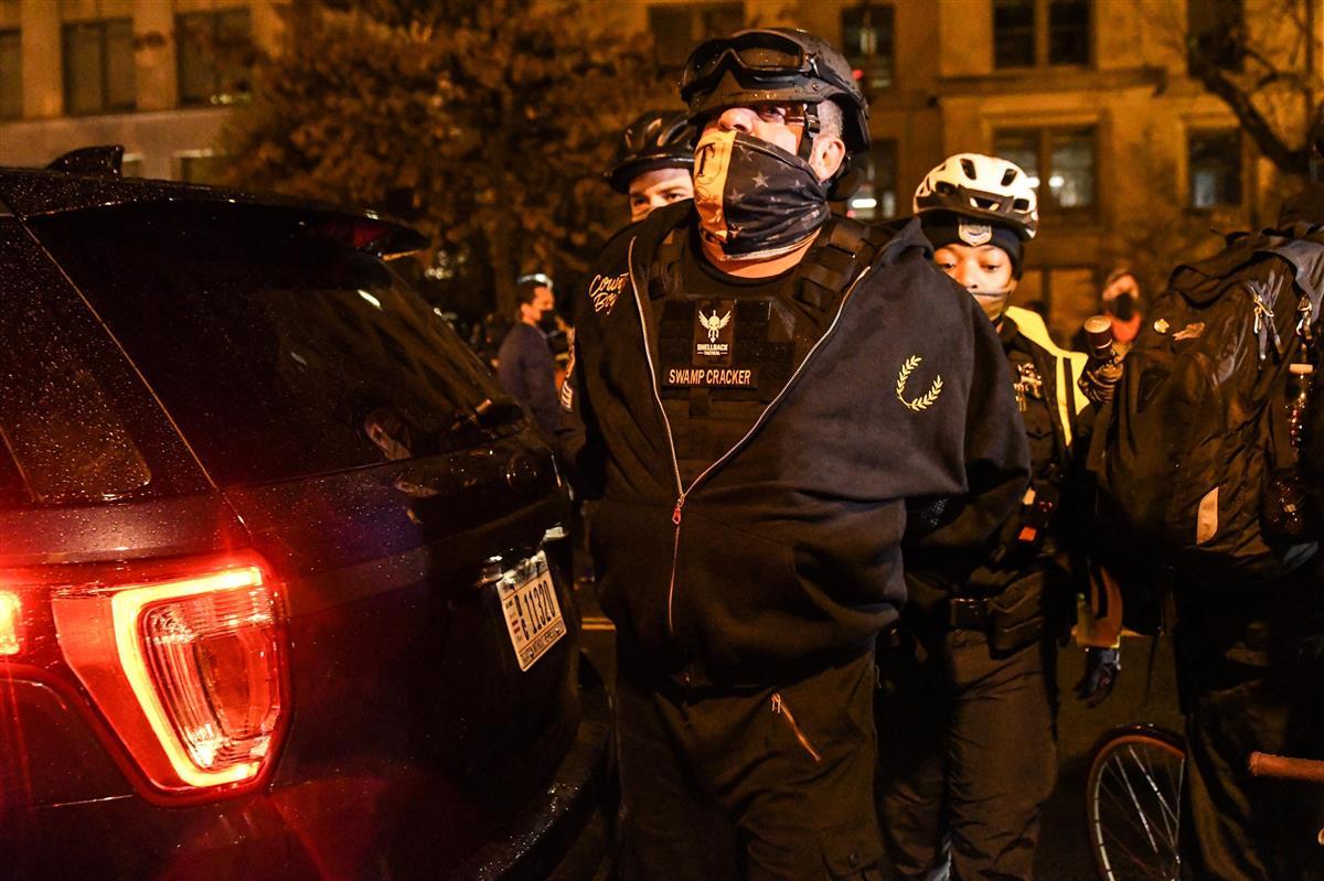 12日、米首都ワシントンで警察に拘束される親大統領の極右組織「プラウド・ボーイズ」のメンバー(ゲッティ=共同)