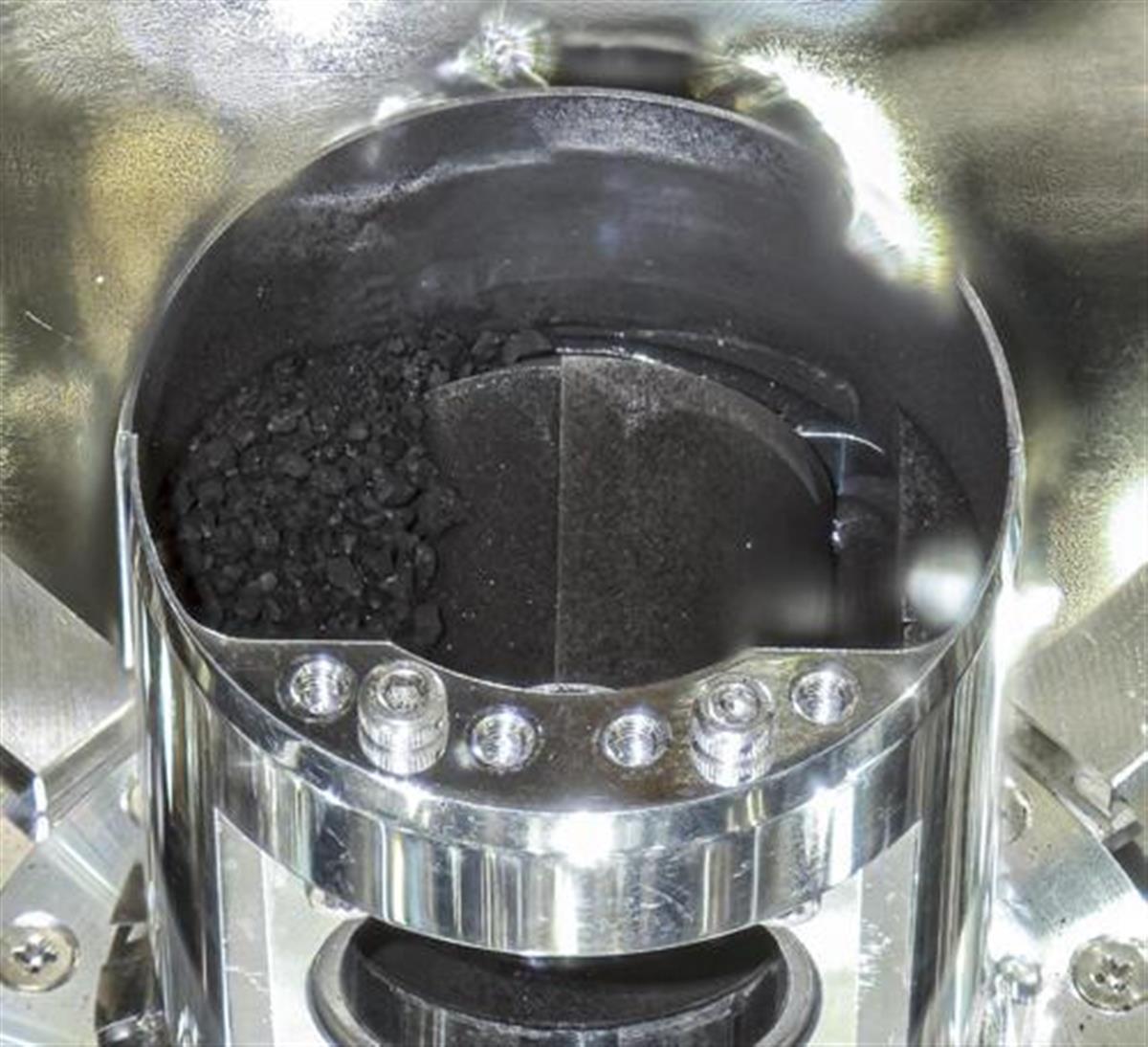はやぶさ2のカプセルで確認された黒い砂つぶ(矢印)(JAXA提供)