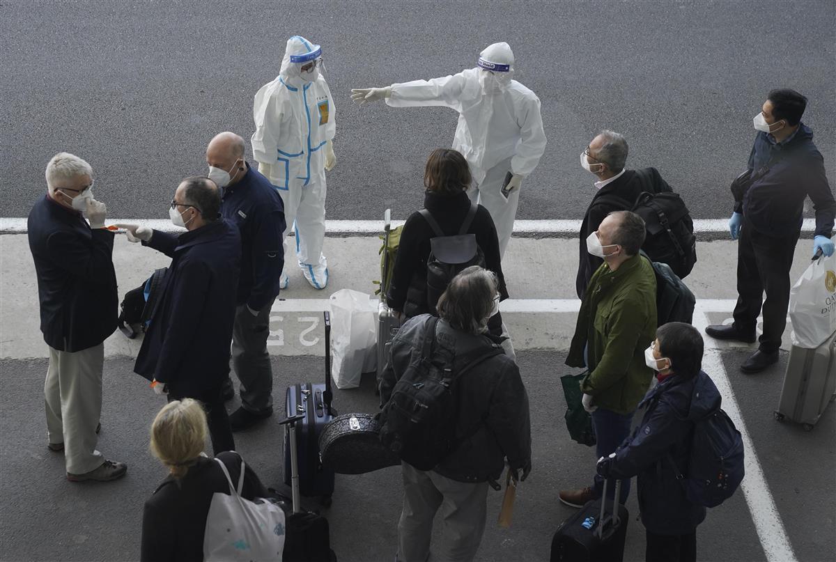 空港に到着した世界保健機関(WHO)の国際調査団に指示する防護服姿のスタッフ=14日、中国・武漢市(AP)