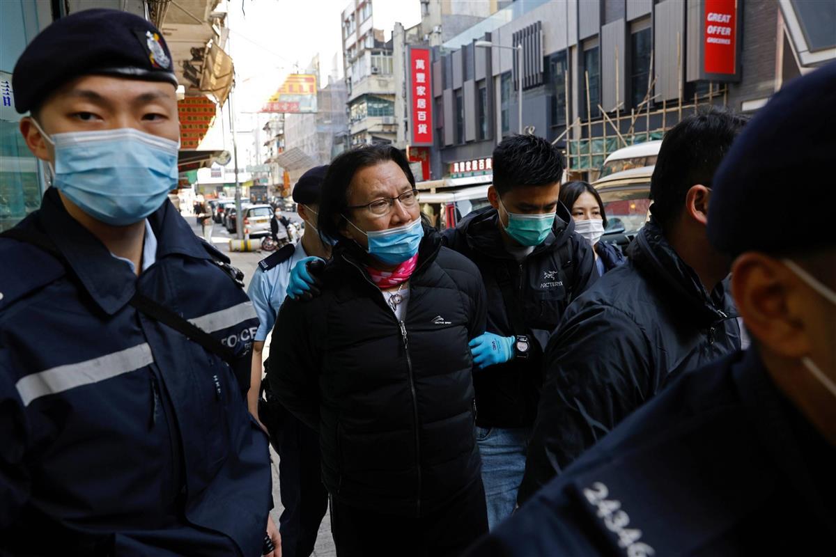 14日、香港で人権派弁護士の黄国桐氏(中央)を連行する警察官(ロイター)