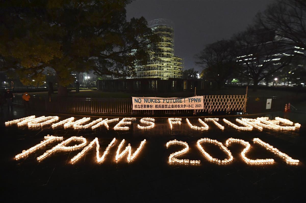 核兵器禁止条約の発効にあわせ、キャンドルを並べて作られた「NO NUKES」などの文字。後方は原爆ドーム=1月22日、広島市の平和記念公園