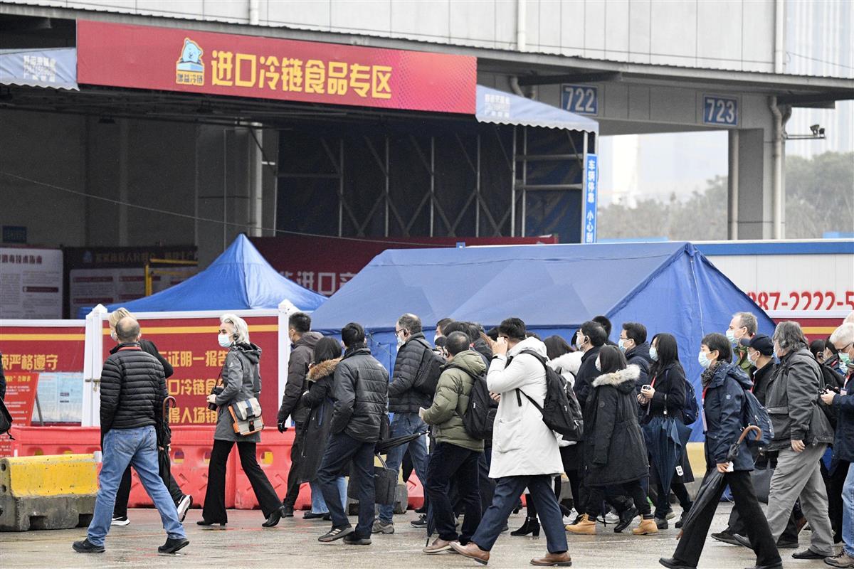 大型卸売市場の倉庫を視察するWHO国際調査団のメンバーら=31日、中国・武漢(共同)