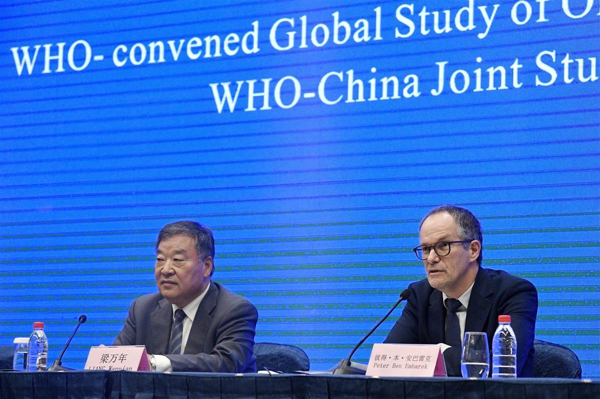 記者会見するWHOの国際調査団のメンバー。中国側の担当者(左)も同席した=9日、中国・武漢(共同)