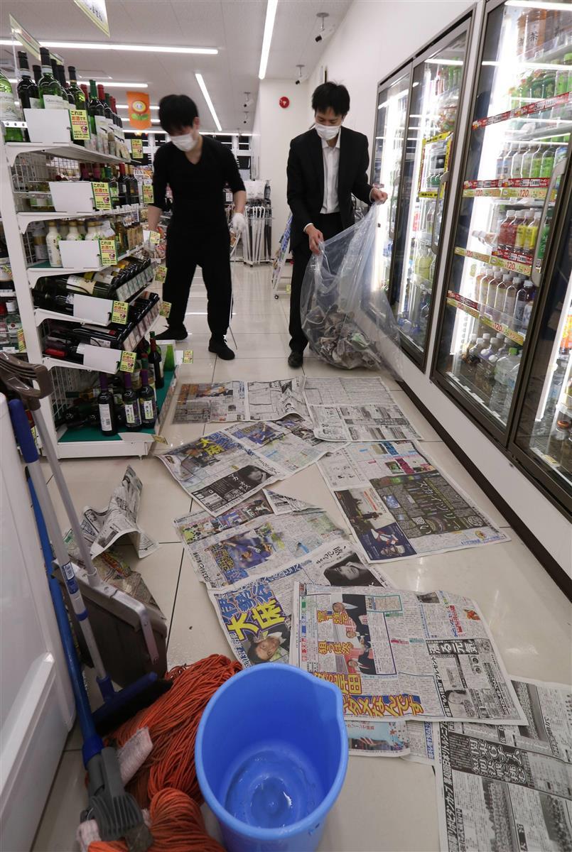 棚から落ちて割れたワインの片付けに追われるセブンイレブンのスタッフたち=14日、福島市(芹沢伸生撮影)