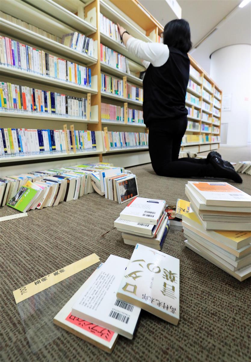 地震に見舞われたいわき市の図書館では、散乱した本の片付けに追われていた=2月14日午前、福島県いわき市(松本健吾撮影)
