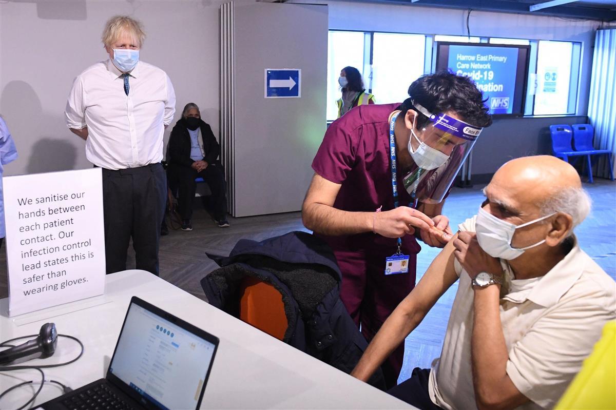 サッカー場での新型コロナウイルス感染症のワクチン接種を視察するジョンソン英首相(左)=1月25日、ロンドン郊外(ゲッティ=共同)