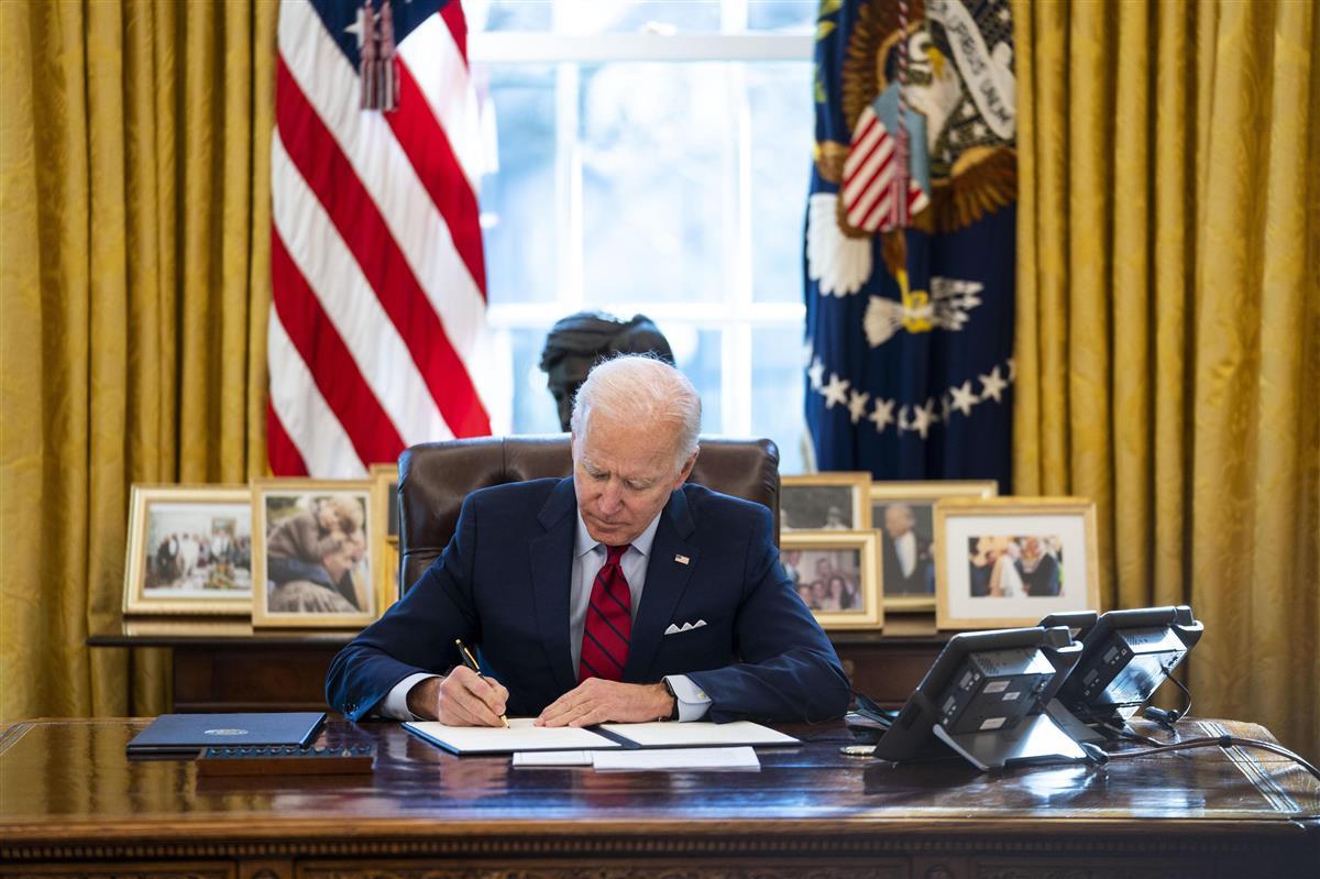 米ホワイトハウスの執務室で大統領令に署名するバイデン氏=1月28日、ワシントン(ゲッティ=共同)