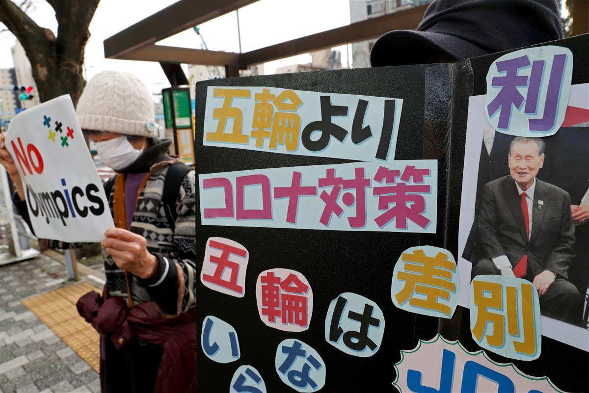 12日、東京で、森氏の写真を掲げて五輪開催に反対する抗議活動の参加者。森氏の発言は欧米メディアの強い関心を集めた(ロイター)