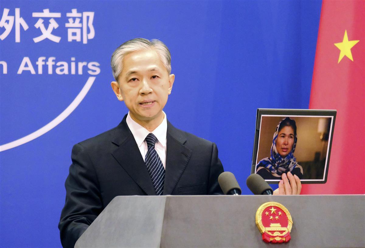 中国新疆ウイグル自治区での性被害を証言した女性の写真を手に「うそつき」と非難する外務省の汪文斌報道官=23日、北京(共同)