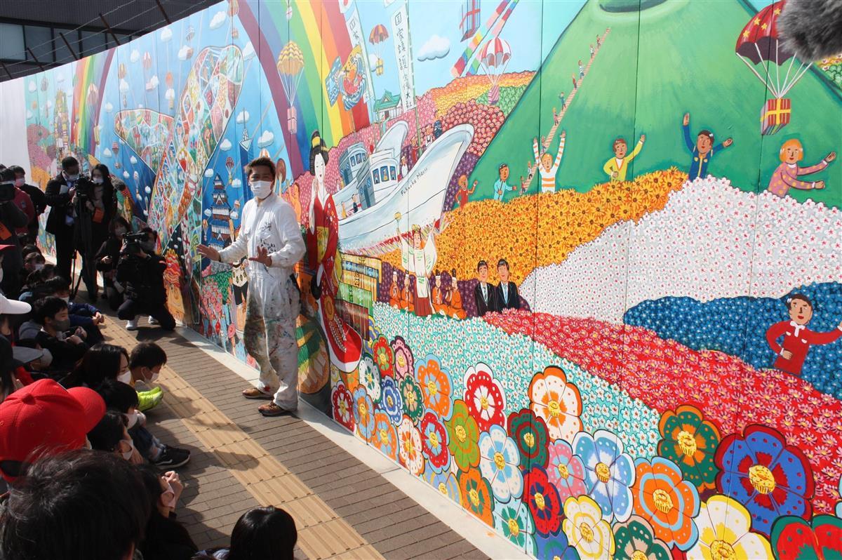 壁画について席田小児童に説明するミヤザキケンスケ氏=福岡空港