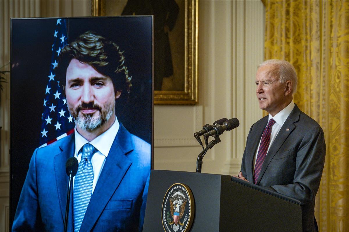 23日、オンライン首脳会談に参加するバイデン米大統領(右)と、モニターに映し出されるカナダのトルドー首相=ワシントン(ゲッティ=共同)