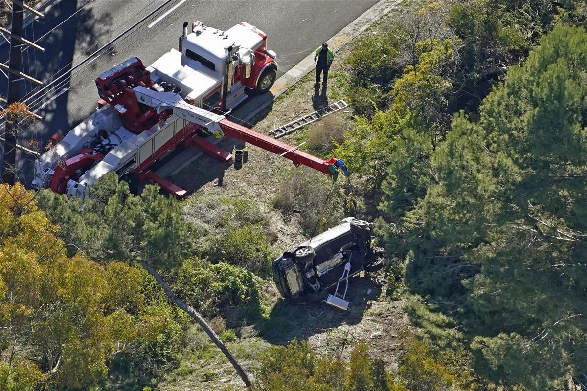 23日、米ロサンゼルス近郊で横転し、クレーンで引き上げられるタイガー・ウッズ選手の車両(AP=共同)