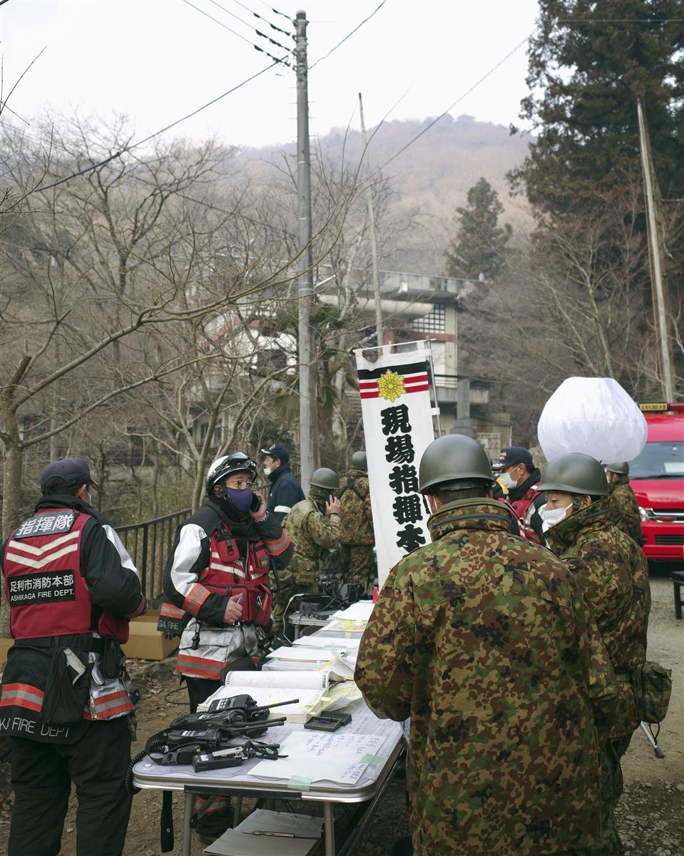 栃木県足利市で起きた山火事で、消火作業の指揮にあたる消防隊員と自衛官ら=25日午前7時20分ごろ