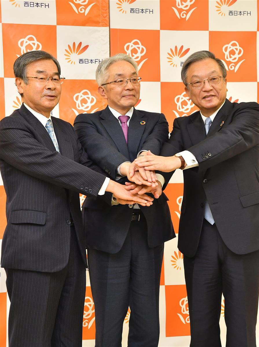 記者会見を終え、ポーズをとる西日本FHの(左から)久保田勇夫氏、村上英之氏、谷川浩道氏