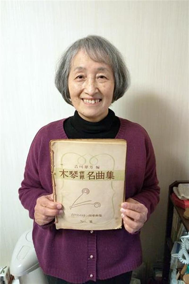 約60年前の木琴のテキストを手に笑顔の桐田勝子さん