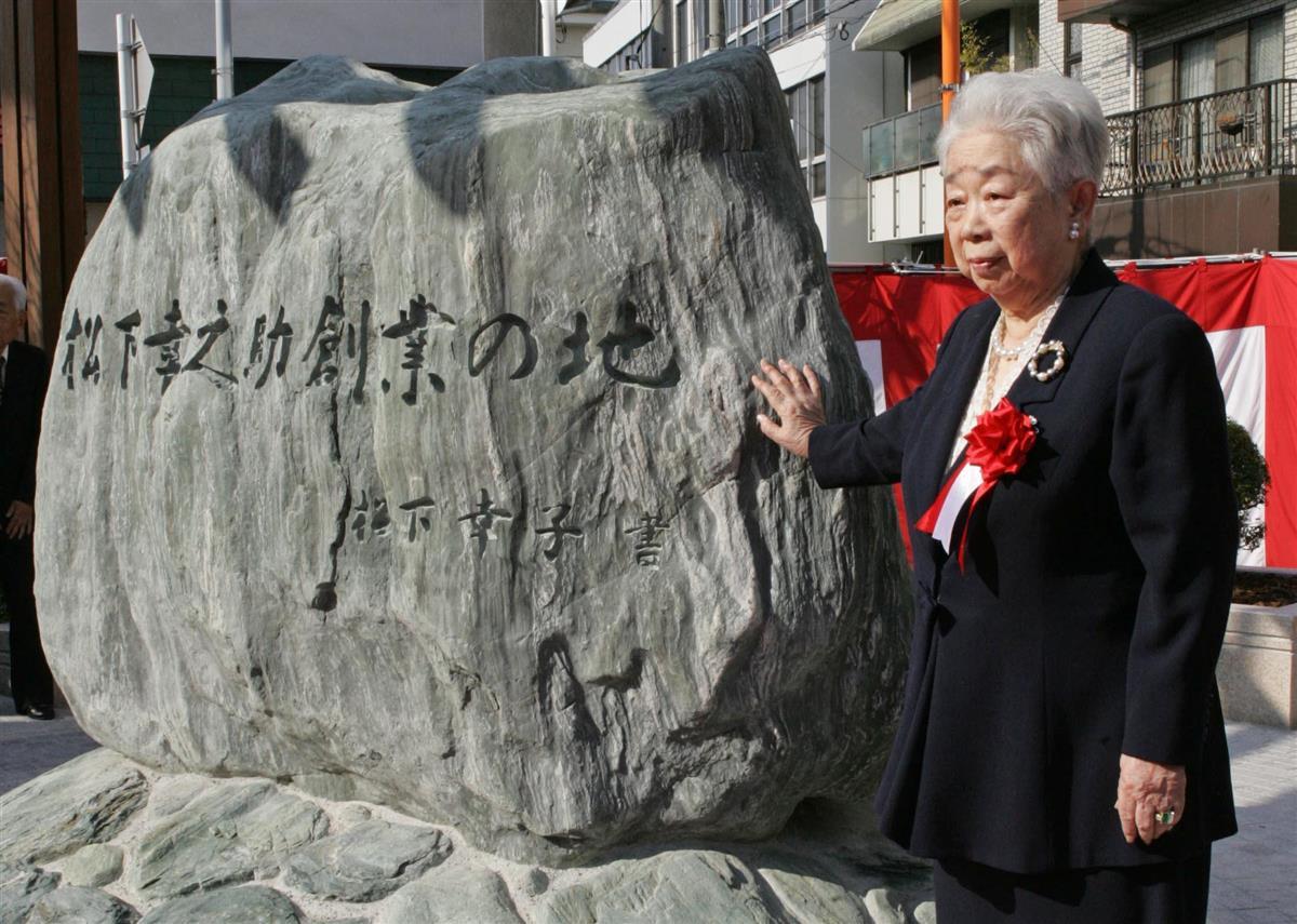 「松下幸之助創業の地」記念碑除幕式。碑の前で記念撮影する松下幸子さん=平成16年11月、大阪市福島区