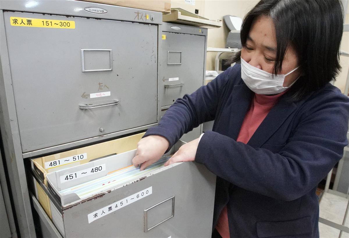 コロナ下で減った求人票を調べる大阪市立泉尾工業高校の女性教諭。「怖いのは来年度以降」という=大阪市大正区(前川純一郎撮影)