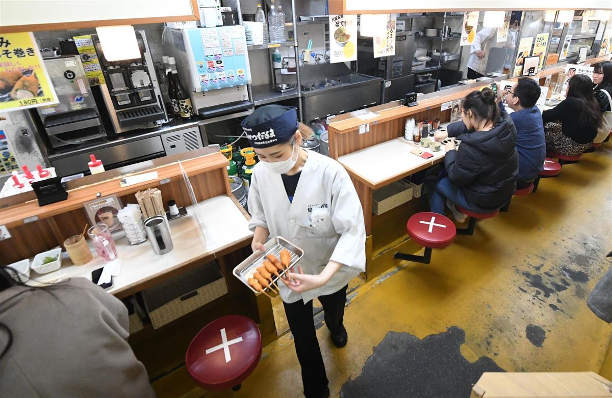 新型コロナウイルスの感染対策で、一部の席に×を付けて間隔を空けている串かつだるま道頓堀店。3月1日からは午後9時閉店にする=27日午後、大阪市中央区(永田直也撮影)