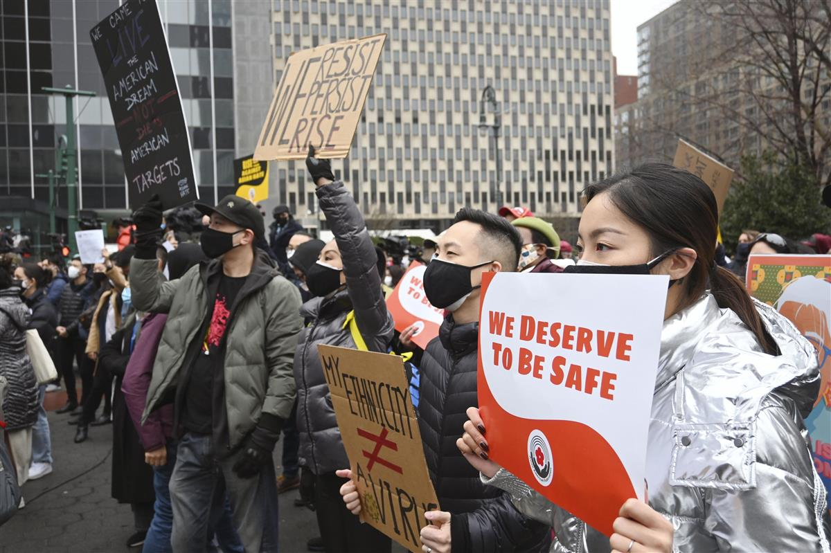 27日、米ニューヨーク市マンハッタンのアジア系差別反対集会で、標語を掲げる参加者(共同)