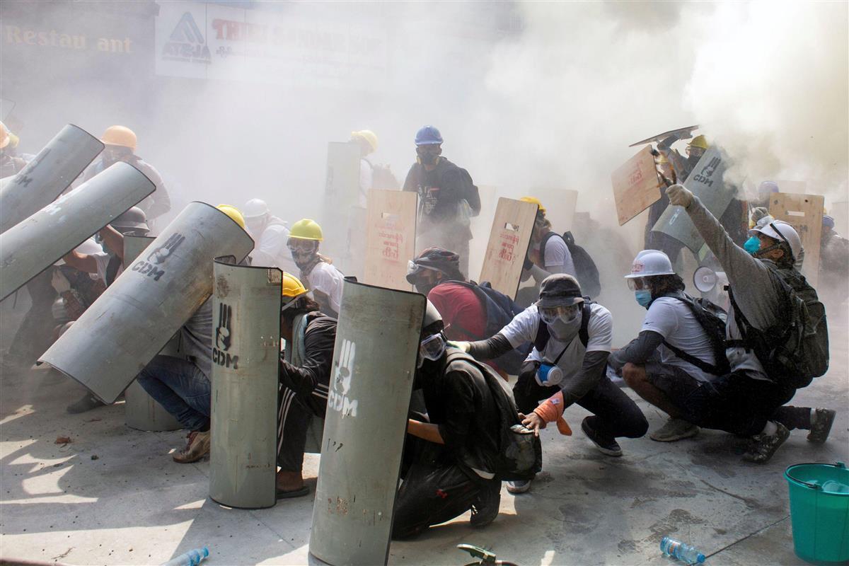 2月28日、ミャンマー・ヤンゴンで治安部隊と衝突し身を守るデモ参加者(ロイター=共同)