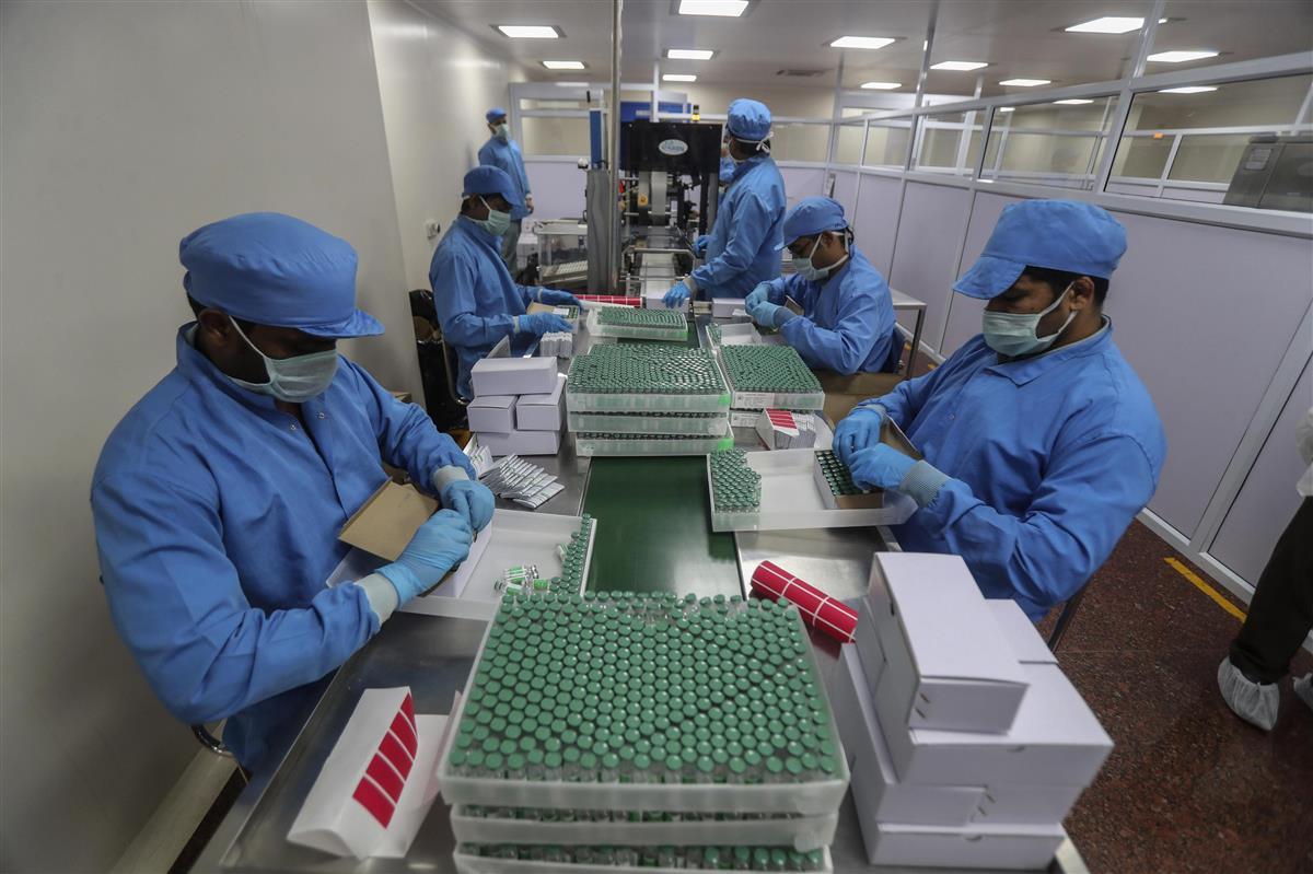 インド西部プネーにある同国企業の工場で、英アストラゼネカの新型コロナワクチンが入った瓶を箱に詰める従業員ら=1月21日(AP=共同)